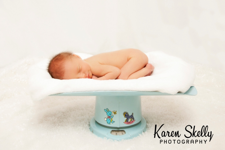 Newborn baby on old fashioned scale by photographers in durango co, durango photographers, durango photography